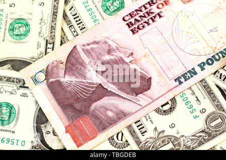 A close up image of an Egyptian ten pound bank note with American one dollar bills in macro - Stock Photo
