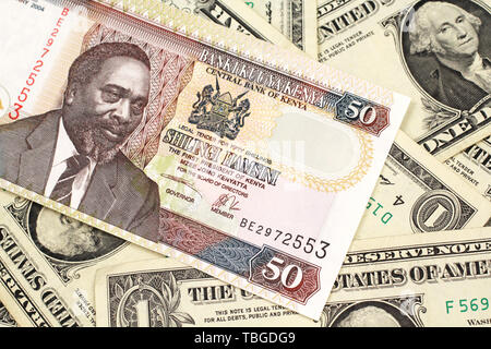A close up image of a fifty Kenyan shilling bank note in macro with American one dollar bills - Stock Photo