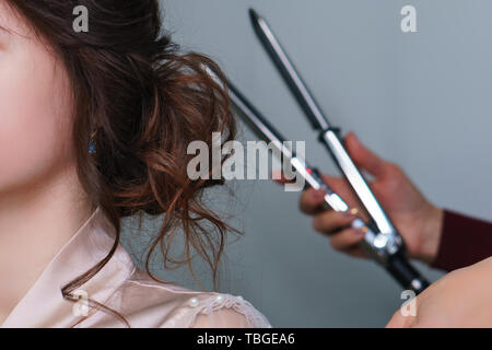 Hands of haircutter do bridal hairstyle with curls for long brown hair closeup. Backstage work of professional hairdresse. Side view of woman with lon - Stock Photo