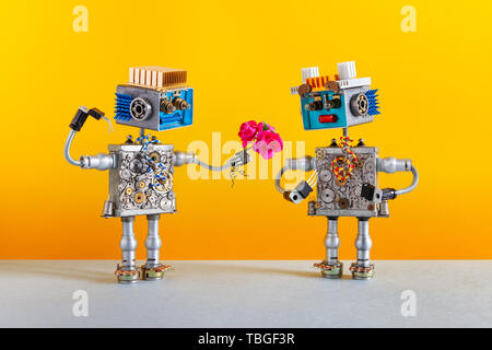 Dates robots. Romantic robot man gives a bouquet of pink roses flowers to a female robot. Dating agency or valentines wedding day card. Yellow backgro - Stock Photo