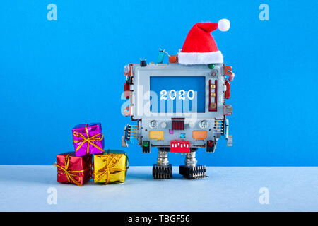 Merry Christmas Happy 2020 year greeting card. Robotic computer Santa Claus red hat and gift boxes and congratulation message 2020 on blue screen. Mod - Stock Photo