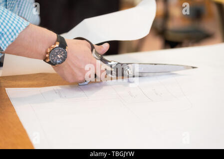 Tailor cutting out the marked pattern on fabric with large scissors on the workbench in his shop, close up view of his hands . - Stock Photo