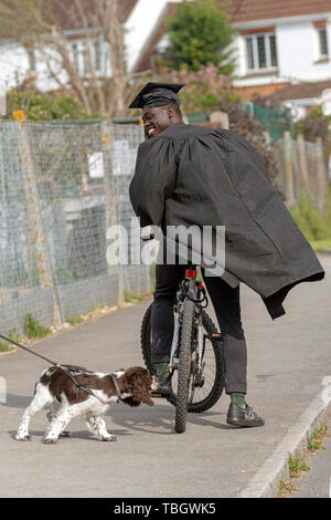 Andover, Hampshire, England, UK. May 2019. A university student wearing cap and gown on a bicycle . Stops on sidewalk to say hi to a spaniel dog - Stock Photo