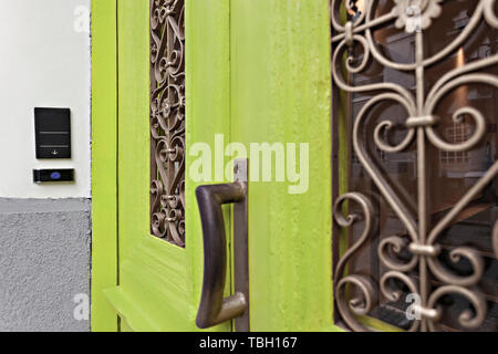 Detail of a doorknob and door intercom of an old green carving antique door in Belgrade, entrance in a hotel - Stock Photo