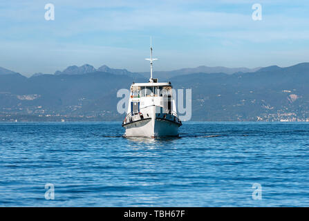 Ferry boat in the Lake Garda (Lago di Garda) in front of the port of Lazise, small town in Veneto, Italy, Europe - Stock Photo