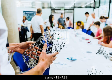 Professor holding in front of his students in biology class a molecular model of a graphene supermaterial. - Stock Photo
