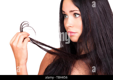 Pretty woman looks at her hair, unhappy with their condition because of split ends, damaged hair concept. Isolated on white background - Stock Photo