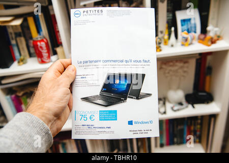 Paris, France - Apr 16, 2019: Man hand holding Dell Computers leaflet advertising distributed to Petites Entreprises Small business featuring new Dell Latitude 5590 laptop library background - Stock Photo
