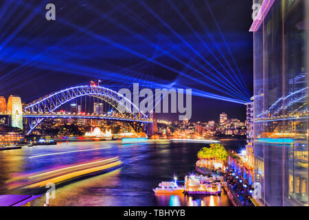 Glass reflection of blue laser lights in dark sky over Sydney harbour and illuminated Sydney harbour bridge from Circular Quay during Vivid Sydney sho - Stock Photo