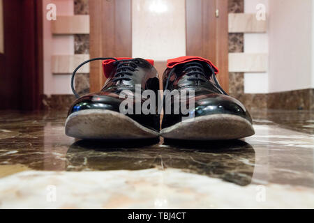 Black patent leather shoes with lacing and red socks inside, are on the black marble floor, close-up shot - Stock Photo