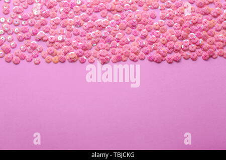 Heap of shiny sequins on color background - Stock Photo