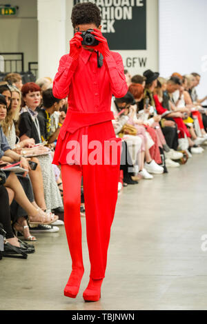 London, UK, 02 June 2019.  Liverpool John Moores University Show. A model walks the runway in  a design by  Riopelle X Ljmu Fashion, a sponsored tailoring project and collaboration of several designers. The models walk with mobile phones and cameras.  Graduate Fashion week is held at the Old Truman Brewery, and a showcase and springboard for new talent from British fashion schools to the international fashion industry. - Stock Photo