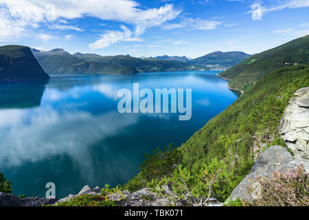 Sky reflecting on the smooth water surface of Storfjorden in Sunnmore region, More og Romsdal, Norway - Stock Photo