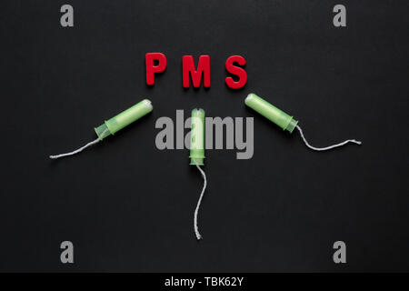 Tampons and text PMS on dark background - Stock Photo
