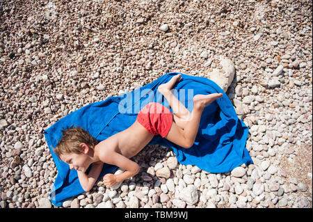 happy funny little kid in red shorts lying on blue towel on pebble summer sunny beach Stock Photo