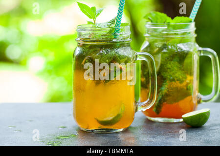 Lemonade, ice tea, infused detox water with lime slices in a jar. Outdoor tropical background. Copy space - Stock Photo