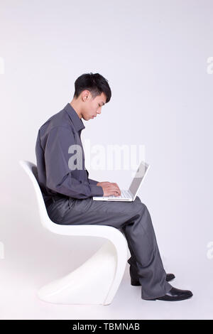 A male white collar is sitting in a chair, - Stock Photo