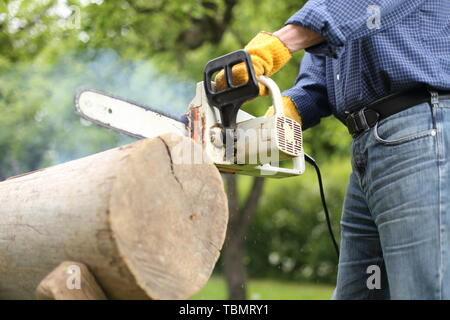 Man working with a Dulled old chain of a Chainsaw - Stock Photo