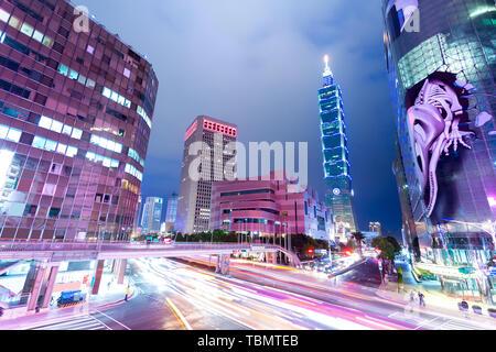 Busy traffic light trails in modern street and illuminated landmark of taipei at night - Stock Photo