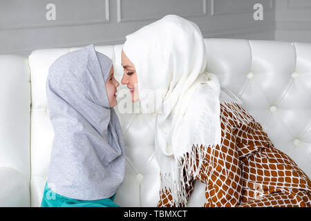 Muslim family mom and daughter in hijabs and traditional clothes are sitting on the sofa at home, gently rubbing with noses and mom is kissing her daughter's hands. - Stock Photo