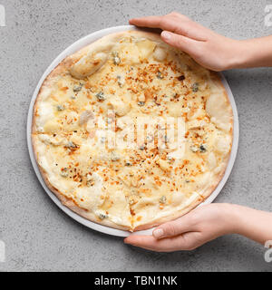Homemade Pizza. Woman Putting Cheesy Pizza On Table - Stock Photo