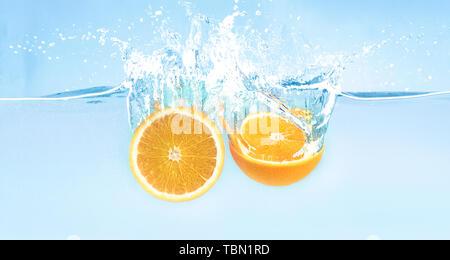 Splash of falling in water fresh orange halves - Stock Photo