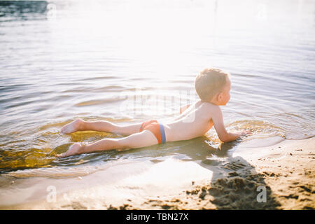 Theme is summer time and rest near the water. Little joyful Caucasian funny boy plays and enjoys in the river. The child is resting and swimming in - Stock Photo