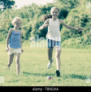 Two small happy girls playing with ball outdoors, running together in summer park - Stock Photo