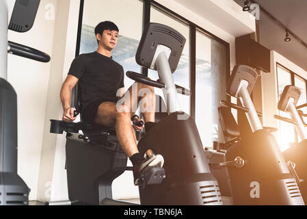 Asian young sport man riding stationary bicycle in fitness gym. Man working out on spinning bikes in gym. People lifestyles and health club concept. B - Stock Photo