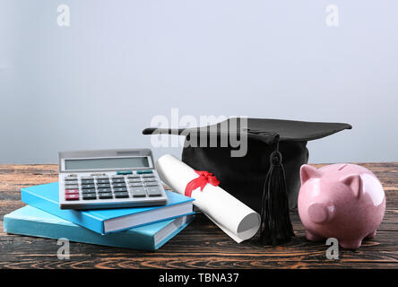 Mortar board, books, calculator, diploma and piggy bank on table. Fee-paying education concept - Stock Photo