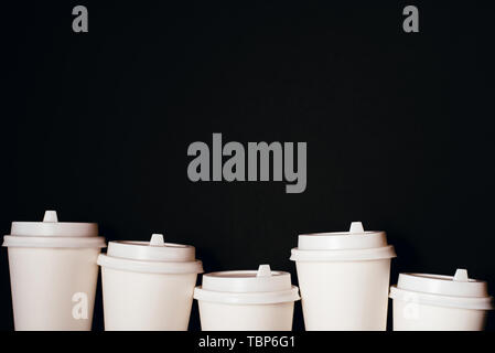 Several paper cups for coffee or tea on black background. Copy space for text. - Stock Photo