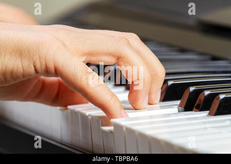 Close up view of kid hands playing on piano keyboard - Stock Photo