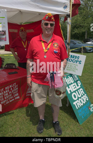 Old Westbury, New York, USA. 2nd June, 2019. PDD Jim Seaman Sr. of the 154 Marine Corps League, Detachment 240, holds small American Flags, and RON STEINER, Commendant of the Detachments is standing behind him, at a booth to raise funds to help U.S. Troops, at the 53rd Annual Spring Meet Antique Car Show, sponsored by the Greater NY Region (NYGR) of the Antique Car Club of America (AACA), at Old Westbury Gardens, a Long Island Gold Coast estate. Credit: Ann Parry/ZUMA Wire/Alamy Live News - Stock Photo