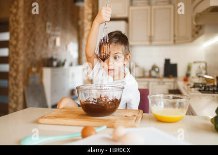 Young kid mixing melted chocolate in a bowl - Stock Photo