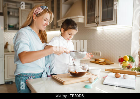 Mother with son mixing melted chocolate in a bowl - Stock Photo