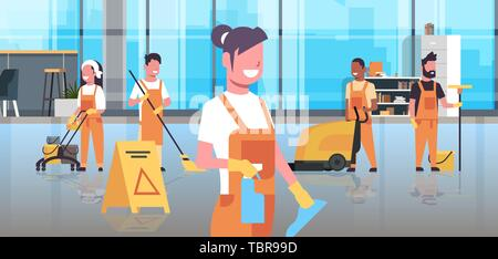 janitors team cleaning service concept cleaners team in uniform working together with professional equipment modern co-working center office interior - Stock Photo