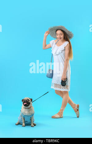 Teenage girl with cute pug dog on color background - Stock Photo