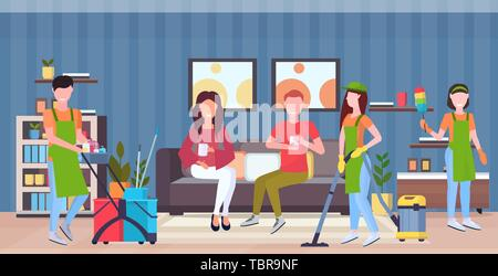 janitors team cleaners in uniform working together with professional equipment cleaning service concept couple sitting on couch modern living room - Stock Photo