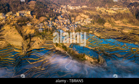 The Yilao Mountain terraces in Yuanyang, Yunnan on March 13, 2019 are the moment of irrigation and raising fields. The sea of clouds steaming on the tree sunrise, the sunset scenery of the eagle mouth is even more charming, and the love spring and blue terraces surround the village. These are breathtaking for tourists.