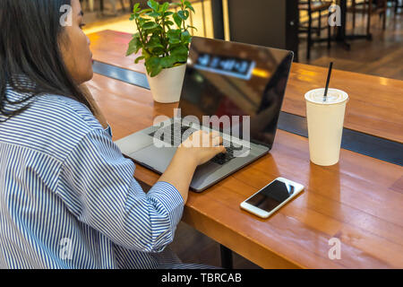 Woman using laptop next to cellphone on table - Stock Photo