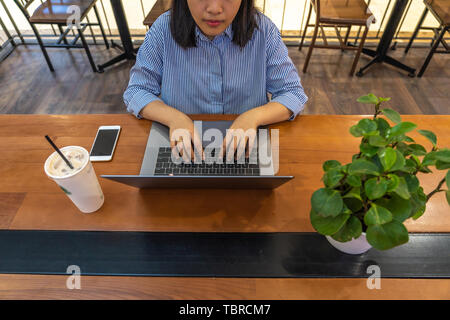Casual student girl using laptop next to cellphone and drink - Stock Photo