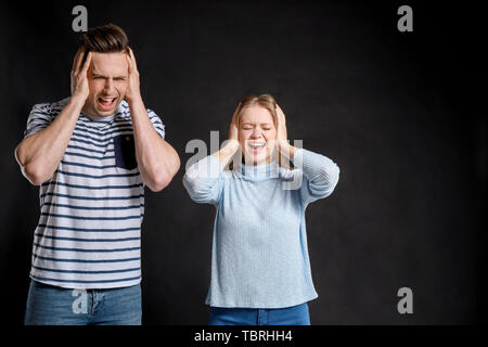 Young quarrelling couple on dark background - Stock Photo