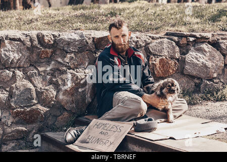 Poor homeless man with dog sitting on stairs outdoors - Stock Photo