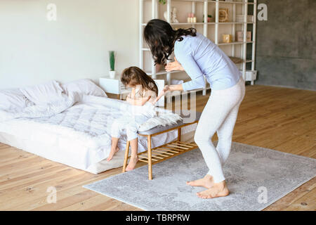 Mother scolding her naughty little daughter at home - Stock Photo