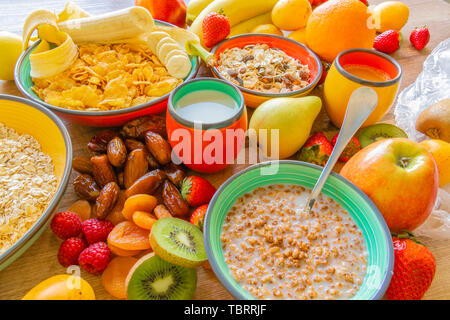 Cereals served in bowls and fruits scattered around the table - Colorful photo - Stock Photo