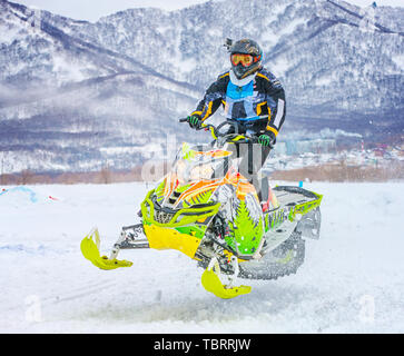 Kamchatka, Russia- 20 APR 2018: Athlete on a snowmobile moving in the winter forest  on the competition 'Snow Way' in the mountains of Kamchatka - Stock Photo