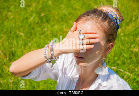 Beautiful boho style woman with accessories enjoy summer sunny day in park. Female hands with bracelets and rings is covering her face. - Stock Photo