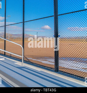 Square frame Sunlit bleachers overlooking a vast sports field on the other side of the fence - Stock Photo