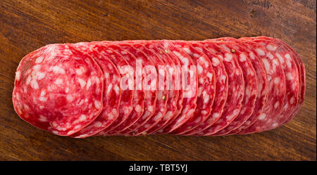 Thin salchichon sausage slices on wooden background, view from above - Stock Photo