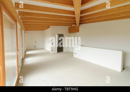 Building site or home renovation in progress: empty open space with large windows and exposed wooden beams - Stock Photo